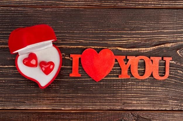Pudełko Z Czerwonego Aksamitu Z Kolczykami. Walentynki Tło Napis Kocham Na Brązowym Tle Drewnianych. Premium Zdjęcia