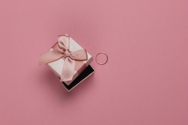 Pudełko Z Kokardą I Złotym Pierścionkiem Na Różowym Pastelowym Tle. Koncepcja ślubu. Biżuteria. Widok Z Góry. Leżał Na Płasko Premium Zdjęcia