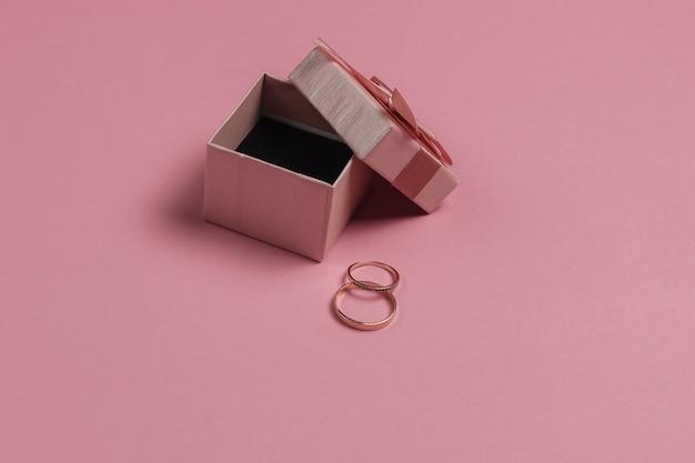 Pudełko Z Kokardą I Złotymi Pierścieniami Na Różowym Pastelowym Tle. Koncepcja ślubu. Biżuteria. Widok Z Góry. Leżał Na Płasko Premium Zdjęcia
