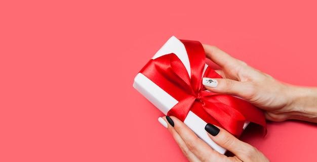 Pudełko Z Kokardą W Rękach Kobiety Na Czerwonej Powierzchni Premium Zdjęcia
