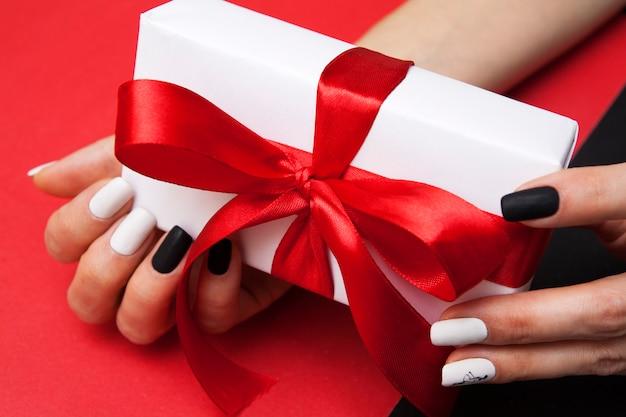 Pudełko Z Kokardą W Rękach Kobiety Z Manicure Premium Zdjęcia