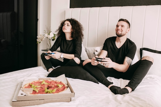 Pudełko z pizzą stoi przed mężczyzną i kobietą grającą na ps na łóżku Darmowe Zdjęcia