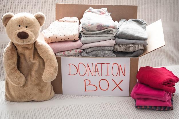 Pudełko Z Ubraniami Na Cele Charytatywne I Misiem Premium Zdjęcia