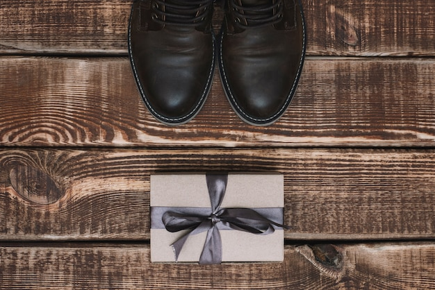 Pudełko Ze Wstążką I Męskie Skórzane Buty Na Drewnianym Stole. Dzień Ojca. Prezent Dla Mężczyzny. Leżał Płasko. Premium Zdjęcia