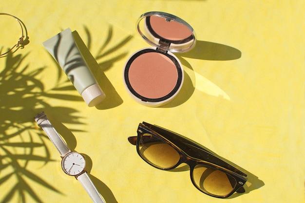 Puder do twarzy foundation blush watch okulary przeciwsłoneczne bransoletka flat lay Premium Zdjęcia