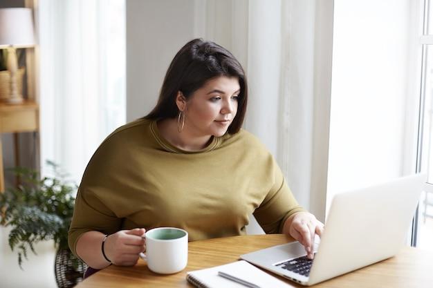 Pulchna Atrakcyjna Młoda Freelancerka Ubrana W Elegancki Sweter I Okrągłe Kolczyki Pracująca Przed Otwartym Laptopem, Siedząca W Przytulnym Wnętrzu Biura Domowego, Pijąca Kawę, Przeglądająca Strony Internetowe Darmowe Zdjęcia