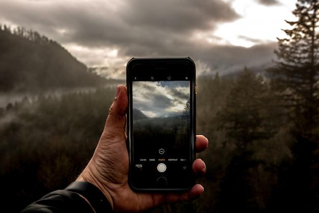 Punkt Widzenia Mężczyzny Trzymającego Smartfon I Fotografującego Piękny Krajobraz Darmowe Zdjęcia