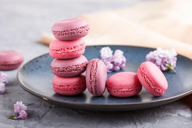 Purpurowi I Różowi Macaron Lub Macaroon Torty Na Błękitnym Ceramicznym Talerzu Na Popielatym Betonowym Tle Premium Zdjęcia