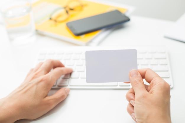 Pusta biała karta kredytowa w dłoni na klawiaturze. Premium Zdjęcia