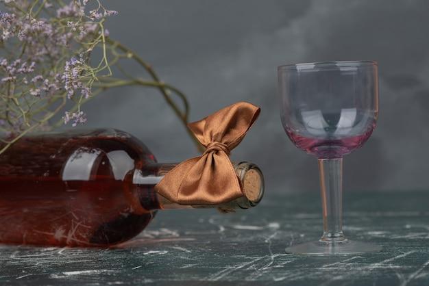 Pusta Butelka I Szkło Z Zwiędłym Kwiatem Na Powierzchni Marmuru. Darmowe Zdjęcia