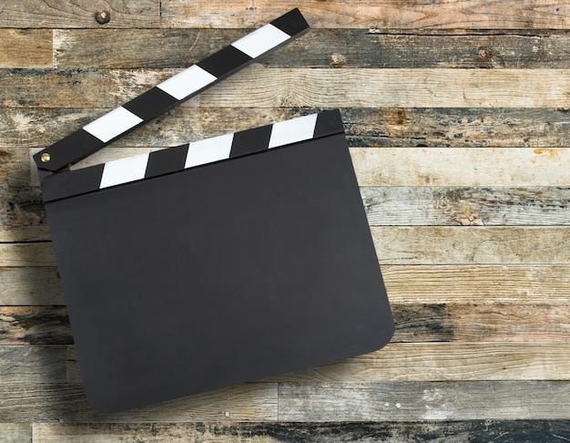 Pusta film produkci clapper deska nad drewnianym tłem z Premium Zdjęcia