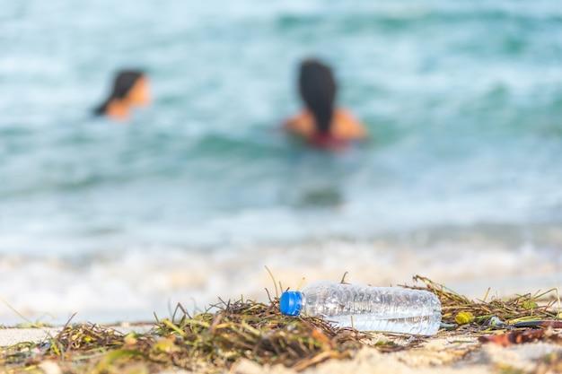 Pusta plastikowa plaża z butelkami wody wypełniona wodorostami, śmieciami i odpadami na brudnej, piaszczystej plaży z ludźmi na morzu Premium Zdjęcia
