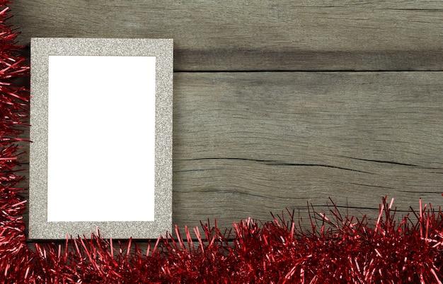 Pusta Ramka Na Zdjęcia Vintage Na Drewnianej Podłodze I Czerwone Frędzle Na Dekoracje świąteczne I Noworoczne Premium Zdjęcia