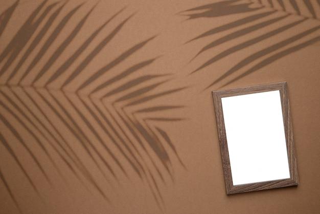 Pusta Ramka Na Zdjęcie Na Brązowym Tle Trendu Ze światłem Cienia Roślin Tropikalnych Jako Szablon Do Promocji Wydarzenia, Prezentacji Projektu, Własnego Portfolio Itp.widok Z Góry Premium Zdjęcia