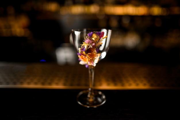 Pusta Szklanka Ozdobiona Różnymi Wielokolorowymi Kwiatami Stojącymi W Barze Premium Zdjęcia
