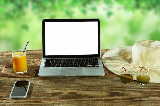 Puste Ekrany Laptopa I Smartfona Na Drewnianym Stole Na Zewnątrz Z Naturą Na ścianie Okulary I świeży Sok W Pobliżu. Koncepcja Kreatywnego Miejsca Pracy, Biznesu, Niezależny. Copyspace. Darmowe Zdjęcia