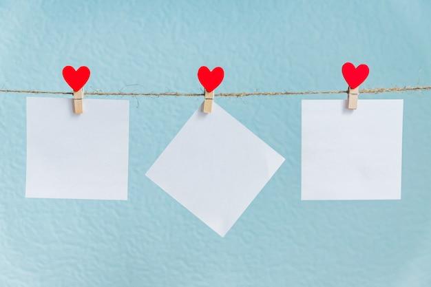 Puste Karty Na Szpilkach Z Czerwonymi Sercami. Makieta Do Tekstu I Niebieskie Tło Dla Pozdrowienia Walentynki Premium Zdjęcia