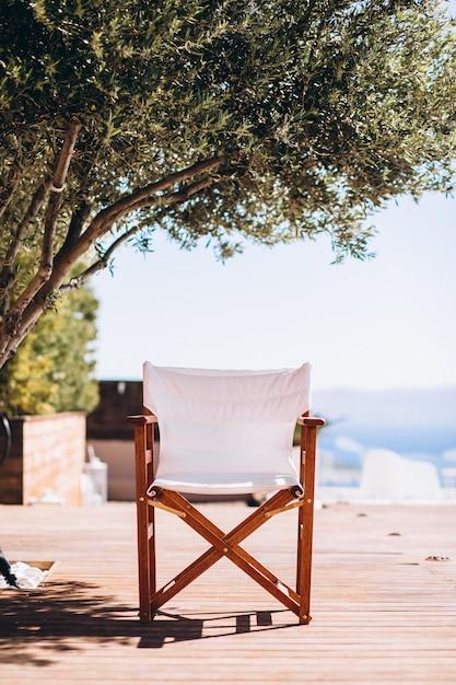 Puste krzesło pod palmą na plaży Darmowe Zdjęcia