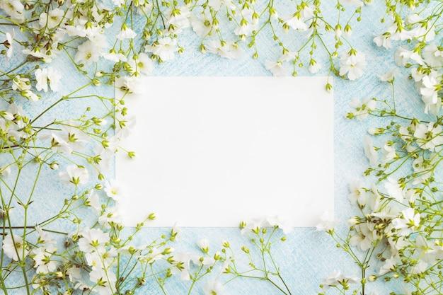 Pusty arkusz papieru otoczony małymi białymi kwiatami. Premium Zdjęcia