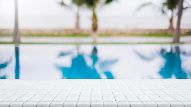 Pusty Biały Blat Z Mozaiki Ceramicznej I Niewyraźny Basen W Tropikalnym Kurorcie Premium Zdjęcia