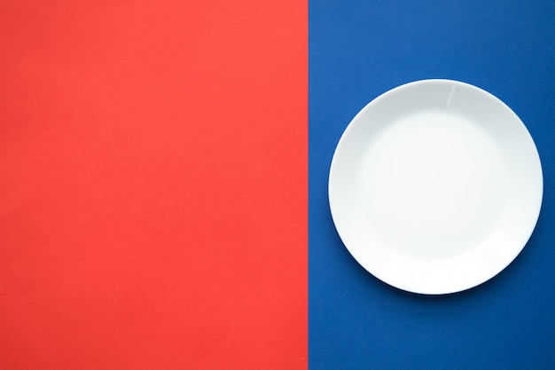 Pusty Biały Talerz Na Czerwono-niebieskim Stole, Stół Do Serwowania Dzieł Sztuki Premium Zdjęcia