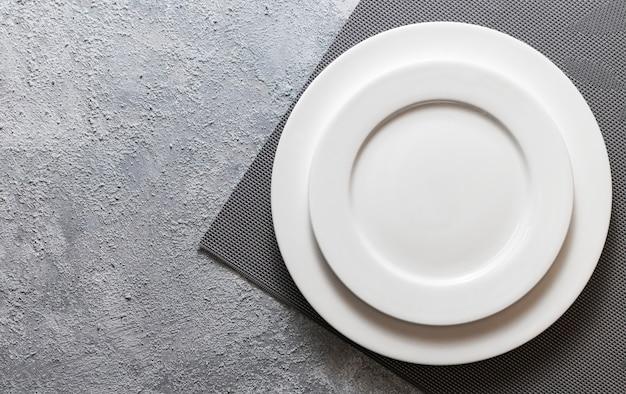 Pusty Biały Talerz Podany Na Reliefowej Serwetce I Wytłoczonym Szarym Tle Betonu. Widok Z Góry Makiety Menu Premium Zdjęcia