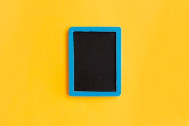 Pusty blackboard z błękitną drewnianą ramą na kolorze żółtym Darmowe Zdjęcia