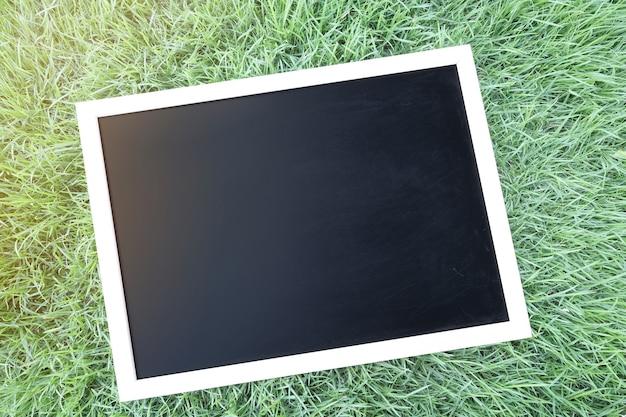 Pusty Czarny Chalkboard Na Trawie. Premium Zdjęcia