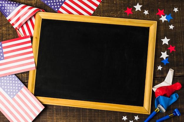 Pusty Czarny łupek Z Amerykańskimi Flagami; Gwiazdy; Balony I Dmuchawy Na Drewniane Teksturowanej Tło Darmowe Zdjęcia