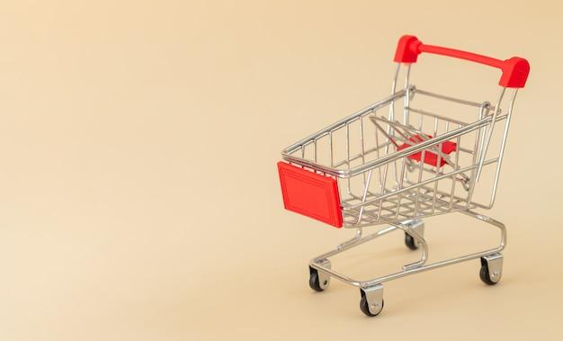 Pusty Czerwony Koszyk Lub Wózek Na Beżowym Tle Z Miejsca Na Kopię Premium Zdjęcia