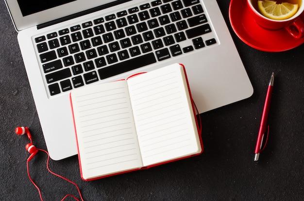 Pusty Czerwony Notatnik, Laptop Komputerowy, Słuchawki I Filiżanka Herbaty. Premium Zdjęcia