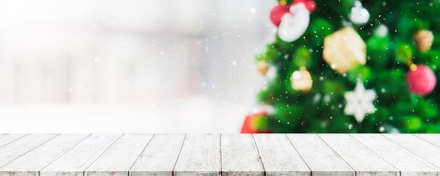 Pusty drewniany stołowy wierzchołek na plamie z bokeh choinki i nowego roku dekoracją na nadokiennym tle Premium Zdjęcia