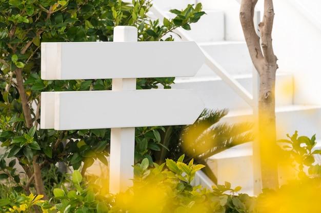 Pusty Drewniany Znak Z Dwa Strzała W Ogródzie Premium Zdjęcia