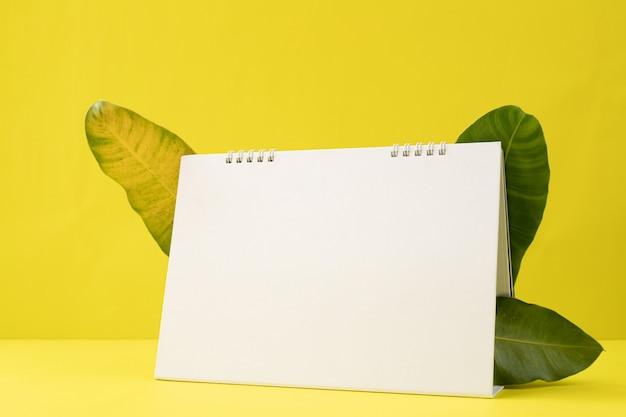Pusty Ekran Papier Kalendarza Na żółtym Tle Z Liśćmi Ramki. Premium Zdjęcia