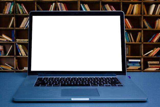 Pusty laptopu ekran z telefonem komórkowym na drewnianym stole przy bookcase tłem Premium Zdjęcia