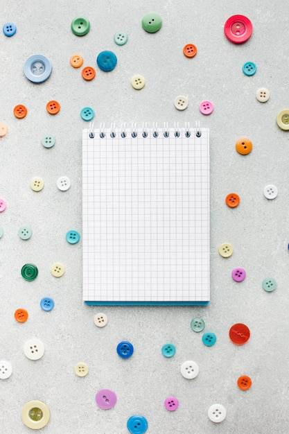 Pusty notatnik otoczony kolorowymi guzikami Darmowe Zdjęcia
