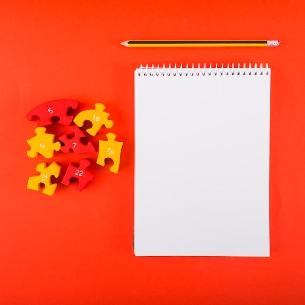 Pusty notatnik z łamigłówkami na czerwień stole Darmowe Zdjęcia