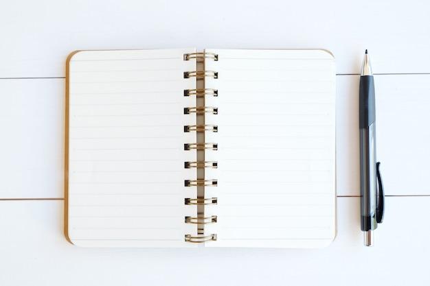 Pusty notatnika papier, pióro na białym drewnianym tle i Premium Zdjęcia