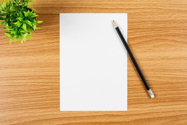 Pusty nutowy papier i ołówek na drewnianym biurku Premium Zdjęcia