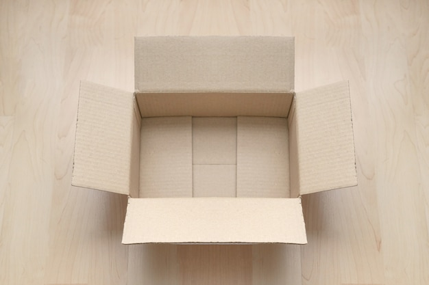 Pusty otwarty prostokątny karton na drewnie. Premium Zdjęcia