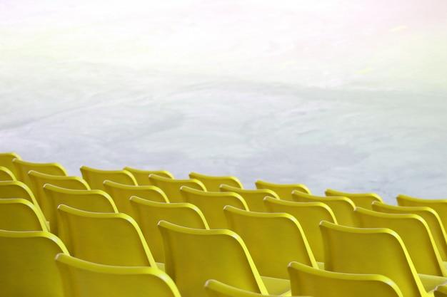 Pusty Plastikowy żółty Siedzenie Wiosłuje Przy Stadium Salowym Przedstawienia Lub Sporta Pola Miejsca Tłem. Premium Zdjęcia