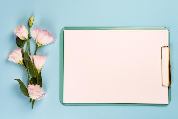 Pusty schowek z papierem i bukietem kwiatów eustoma, widok z góry Premium Zdjęcia