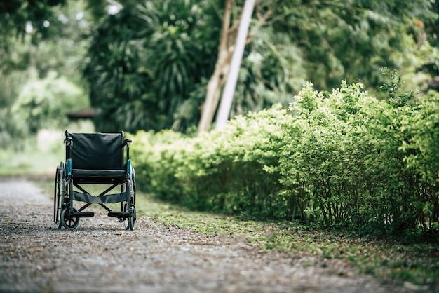 Pusty wózek inwalidzki parkujący w parku, opieki zdrowotnej pojęcie. Darmowe Zdjęcia