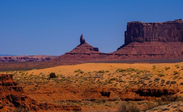 Pustynne Wzgórze Z Suszonymi Krzakami I Klifami W Oddali W Słoneczny Dzień Darmowe Zdjęcia