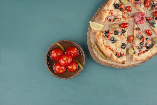 Pyszna Gorąca Pizza I Miska Marynowanych Pomidorów Na Niebieskim Stole. Darmowe Zdjęcia