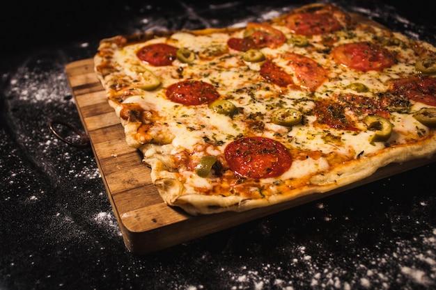 Pyszna Pizza Na Drewnianej Desce, Na Czarnej Powierzchni Premium Zdjęcia
