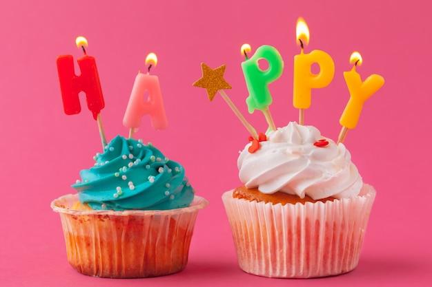 Pyszne babeczki ze świecami na kolorowym tle. świąteczne tło, urodziny Premium Zdjęcia