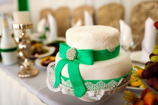 Pyszne białe ciasto w formie czapki z zieloną wstążką i kokardą na stole Premium Zdjęcia