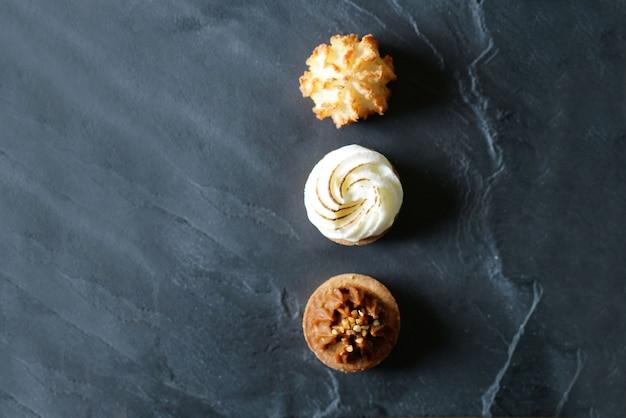 Pyszne Francuskie Mini Torty Ustawione Na Czarnym łupku Z Przestrzenią Tekstową Premium Zdjęcia