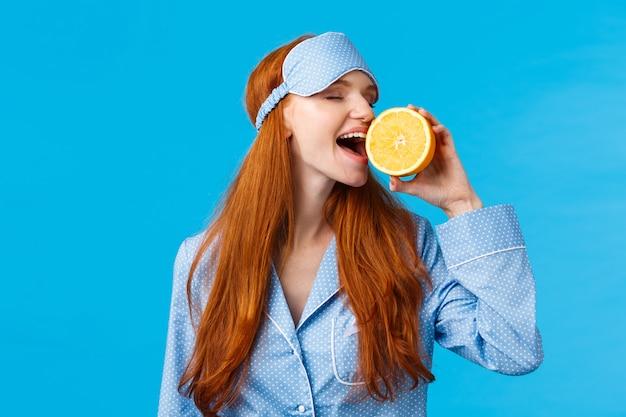 Pyszne Owoce Od Rana Zdrowe. Portret W Talii Atrakcyjna śpiąca, ładna Ruda Dziewczyna W Masce I Nocnej Snu, Gryzący Kawałek Pomarańczy Jedzący Smacznie, Stojący Niebieska ściana Premium Zdjęcia